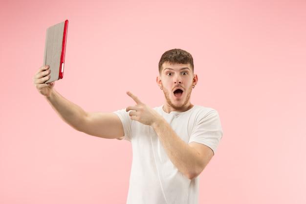 Portret van glimlachende mens die op laptop met leeg scherm richt dat op roze studioachtergrond wordt geïsoleerd. menselijke emoties, gezichtsuitdrukkingsconcept en reclameconcept.