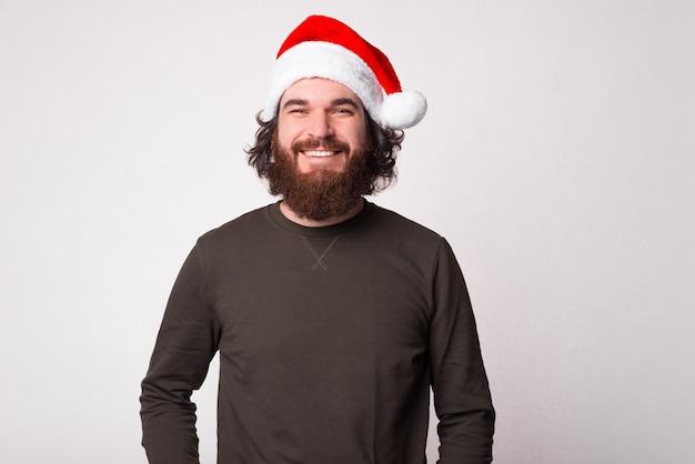 Portret van glimlachende mens die zelfverzekerd de camera bekijkt en de kerstman glb draagt