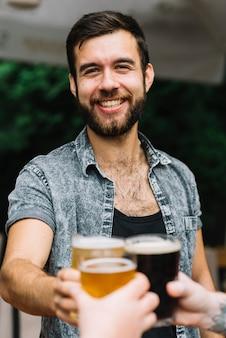 Portret van glimlachende mensen roosterende glazen bierglazen met zijn vriend