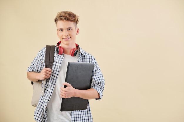 Portret van glimlachende middelbare schoolstudent die met laptop en rugzak voorzijde bekijken