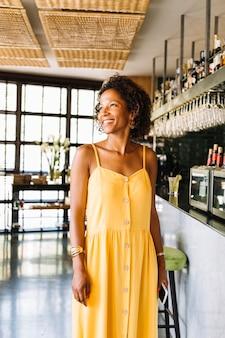 Portret van glimlachende modieuze jonge vrouw die zich in het restaurant bevindt