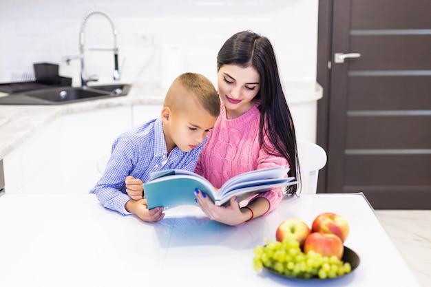 Portret van glimlachende moeder die zoon met huiswerk helpt en goede tijd in keuken heeft