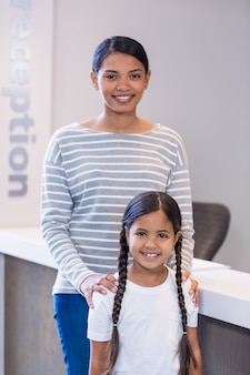 Portret van glimlachende moeder en dochter die zich bij teller bevinden