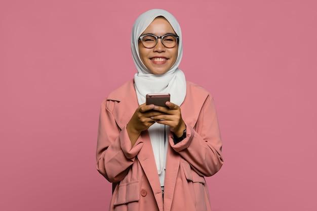 Portret van glimlachende mooie aziatische vrouw die een mobiele telefoon houdt
