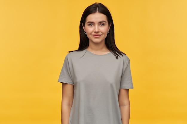 Portret van glimlachende mooie jonge vrouw met donker haar in grijs t-shirt dat over gele muur staat yellow