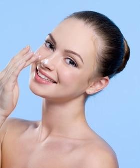 Portret van glimlachende mooie jonge vrouw met room op haar neus op blauw
