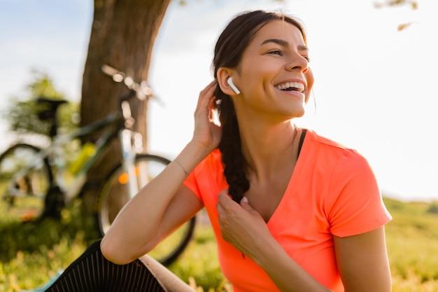 Portret van glimlachende mooie vrouw die sporten in ochtend in park doet