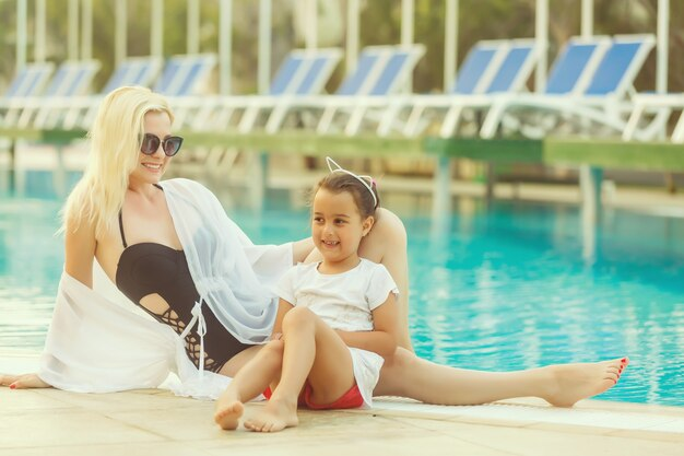 Portret van glimlachende mooie vrouw en haar kleine leuke dochter in zonnebril dichtbij pool openlucht