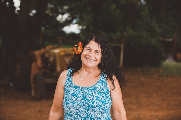 Portret van glimlachende mooie vrouw in aard met bloem op haar haar