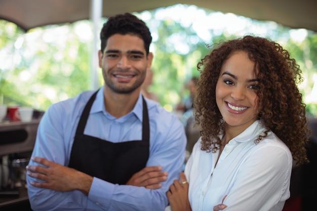 Portret van glimlachende ober en serveerster die zich met wapens bevinden die aan balie worden gekruist