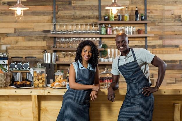 Portret van glimlachende ober en serveerster leunend op de balie