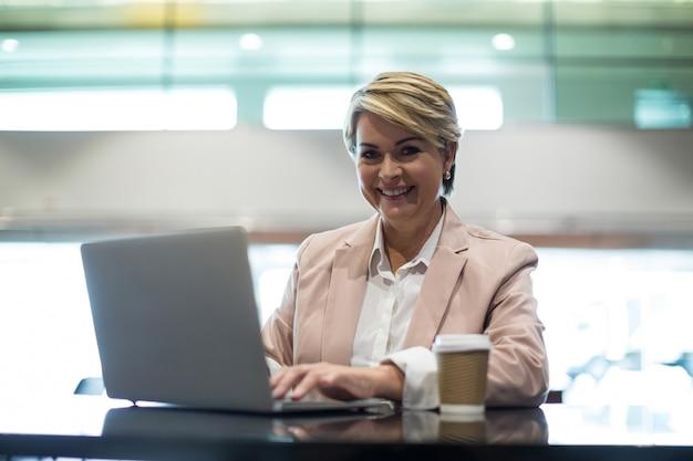 Portret van glimlachende onderneemster die laptop in wachtruimte met behulp van