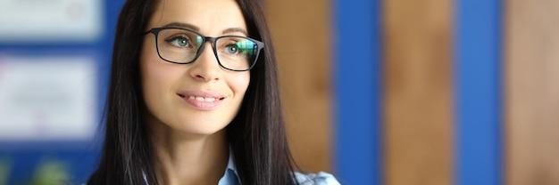 Portret van glimlachende onderneemster met glazen in bureau.
