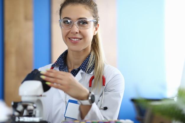 Portret van glimlachende onderzoekswetenschapper met microscoop