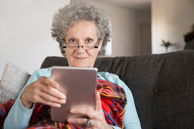 Portret van glimlachende oude dame die digitale tablet in woonkamer gebruiken