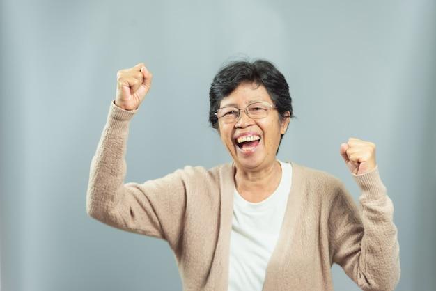 Portret van glimlachende oude vrouw op grijs