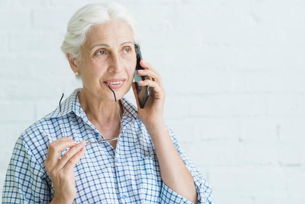 Portret van glimlachende oudere jonge vrouw die op mobiele telefoon spreekt