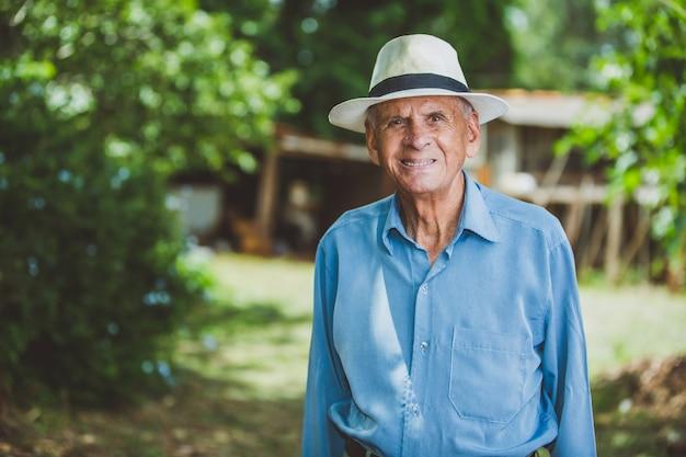 Portret van glimlachende oudere mannelijke landbouwer met hoed