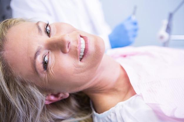 Portret van glimlachende patiënt tegen tandarts