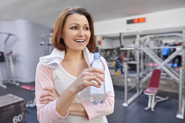 Portret van glimlachende rijpe vrouw met handdoek drinkwater