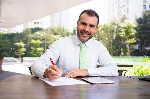 Portret van glimlachende rijpe zakenman die overeenkomst in openlucht ondertekent