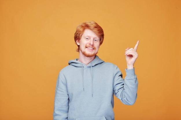 Portret van glimlachende roodharige creatieve it-manager in hoodie die omhoog wijst terwijl het hebben van idee, oranje