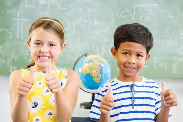 Portret van glimlachende schooljonge geitjes die duimen in klaslokaal tonen