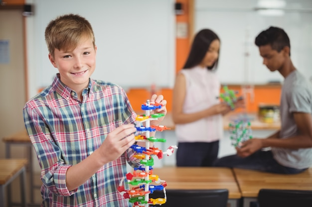 Portret van glimlachende schooljongen die het moleculemodel in laboratorium onderzoekt
