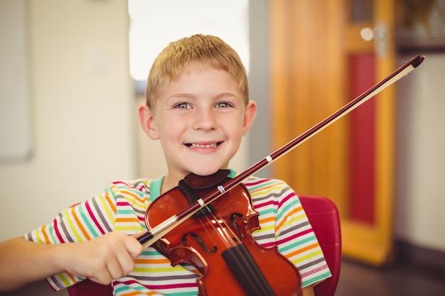 Portret van glimlachende schooljongen het spelen viool in klaslokaal