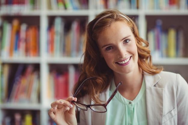 Portret van glimlachende schoolleraar in bibliotheek