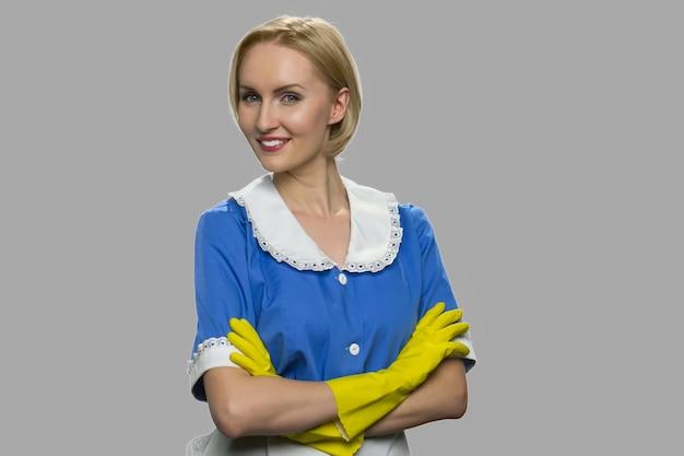 Portret van glimlachende schoonmaakster met gekruiste armen. jonge mooie meid die camera tegen grijze achtergrond bekijkt.