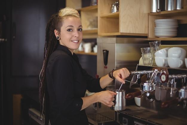 Portret van glimlachende serveerster die de koffiemachine met behulp van