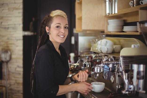 Portret van glimlachende serveerster die een kop van koffie voorbereiden