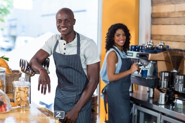 Portret van glimlachende serveerster en ober werken bij balie