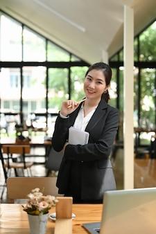 Portret van glimlachende slimme aantrekkelijke jonge vrouw die zich in lobby bevindt en camera bekijkt.