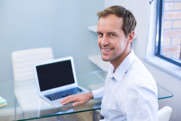 Portret van glimlachende tandarts die aan laptop werkt