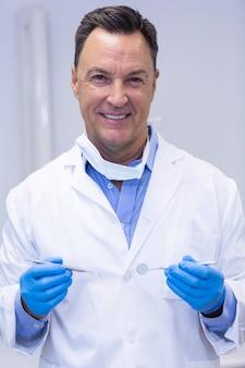 Portret van glimlachende tandarts die tandhulpmiddelen houdt