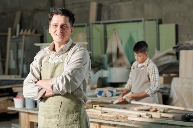 Portret van glimlachende tevreden vader van middelbare leeftijd in schort die zich met gekruiste wapens in timmerwerkwinkel bevinden