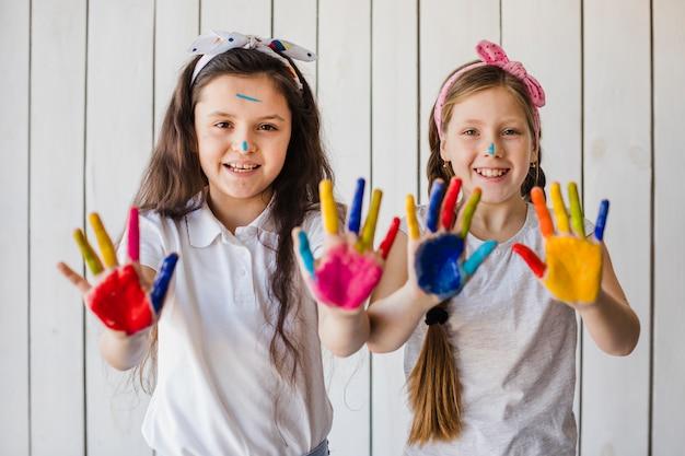 Portret van glimlachende twee meisjes die kleurrijke geschilderde handen tonen die aan camera kijken