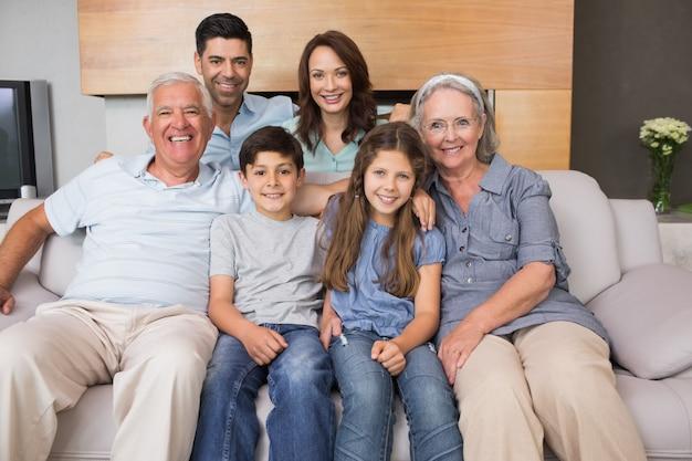 Portret van glimlachende uitgebreide familie op bank in woonkamer