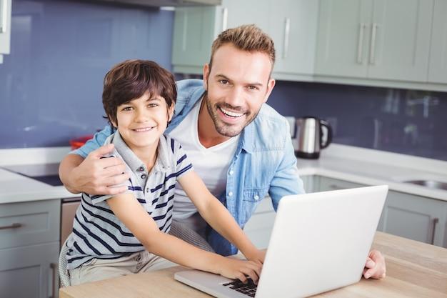 Portret van glimlachende vader en zoon die laptop met behulp van