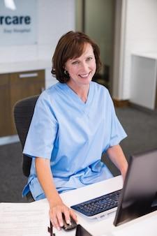 Portret van glimlachende verpleegster die bij bureau werkt