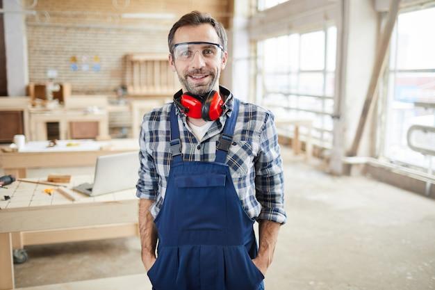 Portret van glimlachende volwassen werknemer in fabriek