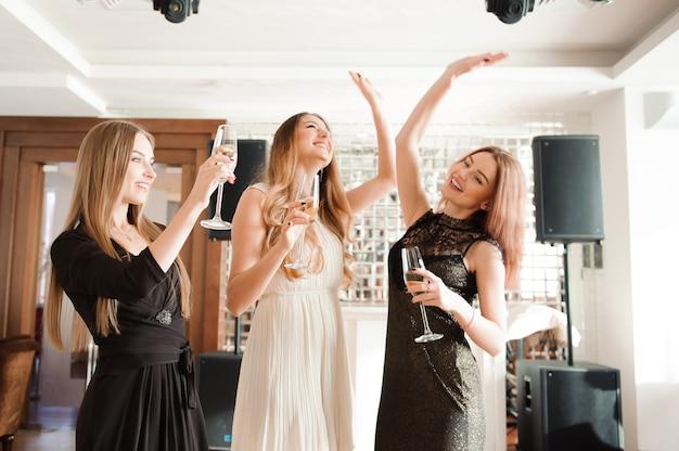 Portret van glimlachende vrienden die glas champagne houden tijdens het dansen bij bar.