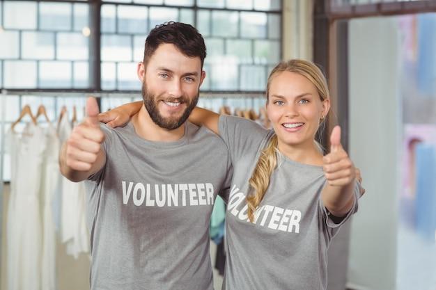 Portret van glimlachende vrijwilligers die duimen in bureau opgeven