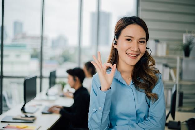Portret van glimlachende vrolijke klantenondersteuning met hoofdtelefoon die ok gebaar toont.