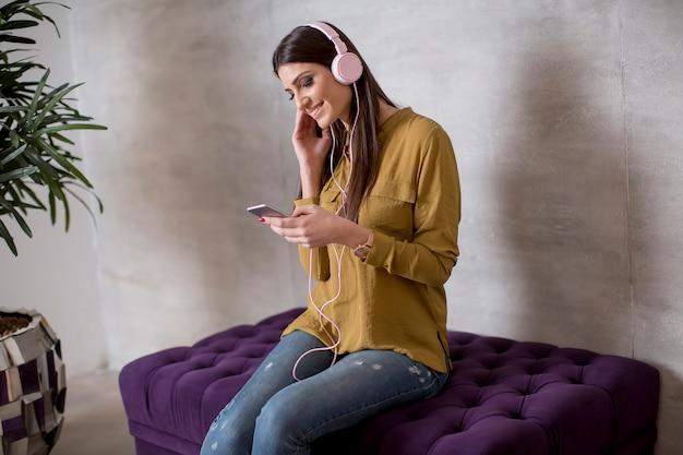 Portret van glimlachende vrouw die en aan muziek op hoofdtelefoon zitten luisteren