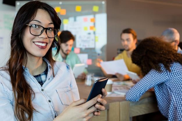 Portret van glimlachende vrouw die haar mobiel op kantoor met behulp van