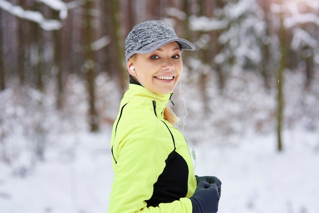 Portret van glimlachende vrouw die in de winter loopt