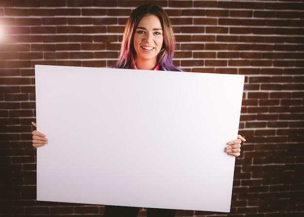 Portret van glimlachende vrouw die leeg aanplakbiljet houdt